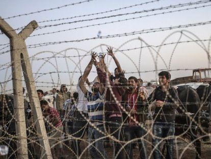Curdos sírios em Suruc, no lado sírio da fronteira, em 21 de setembro. / Foto: AFP | Vídeo: ATLAS