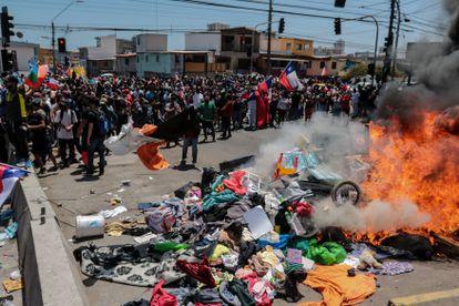 Grupo de pessoas queima barracas que eram utilizadas por estrangeiros para pernoitar em praças e praias, durante passeata contra a imigração irregular no sábado, em Iquique (Chile).