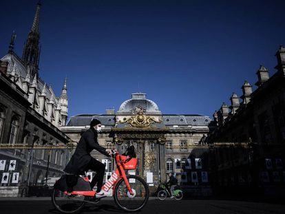 Homem passa de bicicleta diante do Palácio da Justiça, na Île de la Cité, Paris, em maio