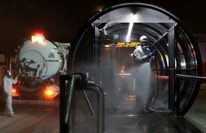 Funcionários dedetizam um ponto de ônibus em Curitiba para evitar a propagação do novo coronavírus.