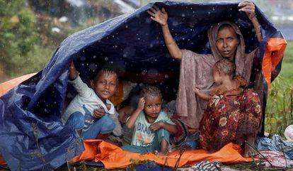 Refugiados da etnia rohingya se protegem da chuva com um plástico no campo de Cox's Bazar, em Bangladesh