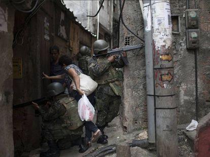 Moradora entra em viela durante incursão policial na favela da Rocinha, no Rio de Janeiro.