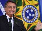 """Brazilian President Jair Bolsonaro gestures during the Launch of the """"Adote 1 Parque"""" (Adopt a Park) Program at Planalto Palace in Brasilia, on February 9, 2021. - The program aims to the contribution of private companies to the maintenance of national parks for environmental preservation. (Photo by EVARISTO SA / AFP)"""