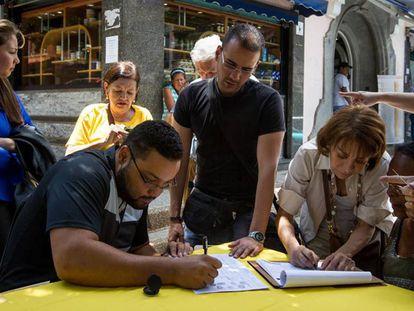 Pessoas coletam assinaturas pela realização de referendo.