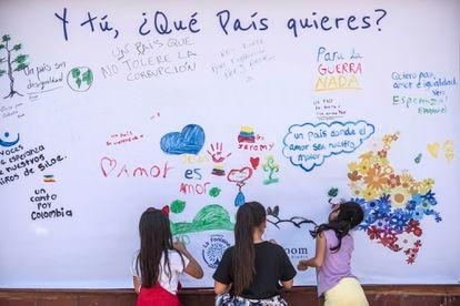 Crianças de um colégio do bairro Siloé (Cali) escrevem frases em um muro.