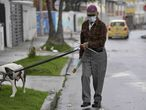 A man wears a face mask as a preventive measure against the spread of the new coronavirus, COVID-19, as he walks his dog in Bogota, on March 16, 2020. - The Colombian government announced the indefinite suspension of face-to-face classes in public schools and universities as a preventive measure against the COVID-19 pandemic. (Photo by Raul ARBOLEDA / AFP)