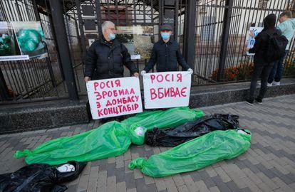 Com bonecos simulando mortos, ativistas seguram cartazes com frases pedindo acesso a vacinas contra a covid-19 na embaixada russa em Kiev, Ucrânia, nesta segunda.