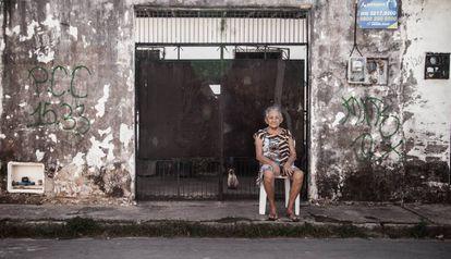Moradora do Pirambu descansa ao lado de pichação do PCC.