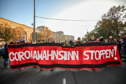 """Protesto do movimento Querdenken, que se opõe às medidas de contenção do coronavírus, em 7 de novembro, na cidade de Leipzig. Na bandeira, lê-se """"Parem com a loucura do coronavírus""""."""