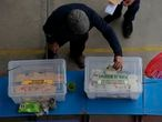 """A residents drops his ballot into a plastic storage container labeled, """"Indigenous people"""", at a polling station during the Constitutional Convention election to select assembly members that will draft a new constitution, in Santiago, Chile, Saturday, May 15, 2021. The face of a new Chile begins taking shape this weekend as the South American country elects 155 people to draft a constitution to replace one that has governed it since being imposed during a military dictatorship. (AP Photo/Esteban Felix)"""
