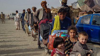 Cidadãos afegãos fazem fila no passo fronteiriço de Chaman, entre o Paquistão e o Afeganistão, nesta terça-feira. Em vídeo, imagens de afegãos tentando sair do país de avião.