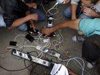 Refugiados carregam seus celulares antes cruzar a fronteira da Macedônia.