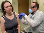 Un investigador inyecta una vacuna de Moderna a una paciente, en un laboratorio de Seattle.
