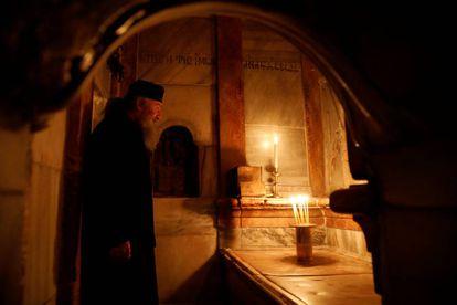 Um padre ortodoxo diante da tumba de Jesus Cristo.
