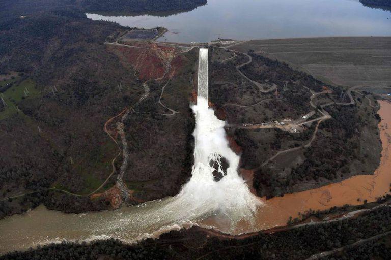 A água se evade com capacidade máxima pelo deságue da represa de Oroville, na segunda-feira. À esquerda, o dique de contenção emergencial danificado.