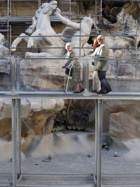 Três visitantes passeiam pela passarela sobre a Fontana de Trevi.