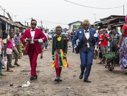 Okili Nkoressa, que passeia com sua mãe e uma amiga, leva um terno de Yves Saint Laurent.