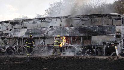 Bombeiros tentam apagar as chamas de um ônibus incendiado em Jalisco.