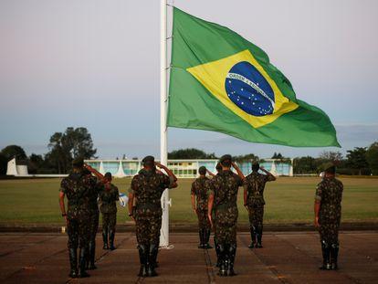 Militares do Exército batem continência para a bandeira do Brasil em frente ao Palácio da Alvorada, residência oficial da Presidência da República, em 7 de julho de 2020.