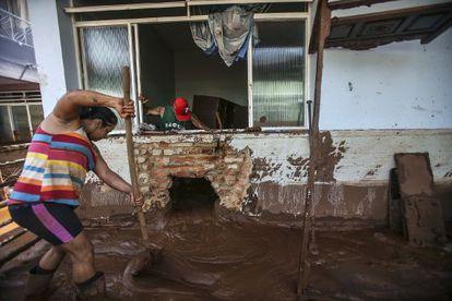 Casal tenta limpar a casa em Barra Longa.