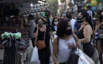 Pessoas caminham usando máscaras de proteção em uma rua de comércio popular no Rio de Janeiro.
