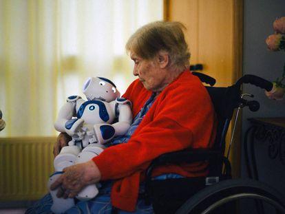 Uma paciente do lar de idosos de Jouarre, próximo a Paris, nina Zora, o robô que lhe faz companhia.