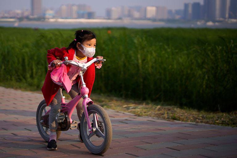 Uma menina anda de bicicleta num parque de Wuhan.