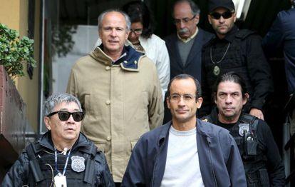 Os empreiteiros Marcelo Odebrecht (de óculos) e Otávio Marques Azevedo escoltados por policiais, em Curitiba.
