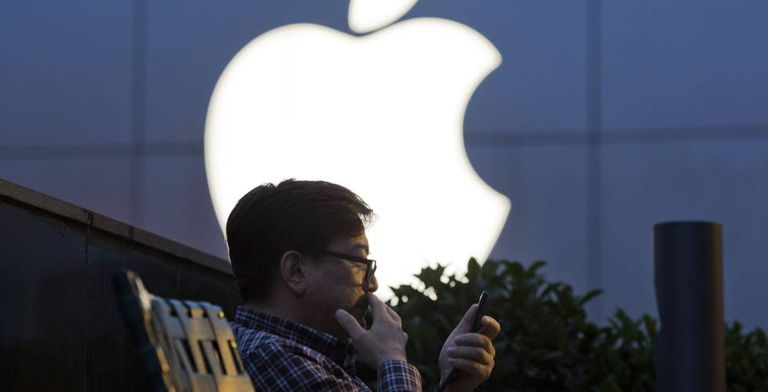 Usuário da Apple em frente a uma loja na China.