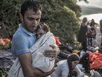 Un hombre abraza y seca a su hijo momentos después de desembarcar en la costa norte de la isla Lesbos tras cruzar el Mar Egeo en un una barca de plástico. Datos de Acnur revelan que el 86% de los refugiados en el mundo está siendo acogido por países en desarrollo.