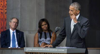 Obama seca uma lágrima diante de Michelle Obama e do ex-presidente George W. Bush.