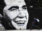 (FILES) In this file photo taken on May 04, 2020 a man rides his bicycle by a mural of tango great Carlos Gardel during the lockdown to slow the spread of the novel coronavirus, COVID-19, in Buenos Aires. - Next June 24 marks the 85th anniversary of Carlos Gardel's death in a plane crash while leaving Medellin to Bogota, during a tour. (Photo by Juan MABROMATA / AFP)