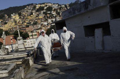 Agentes funerários carregam o corpo de Avelino Fernandes Filho, 74, que morreu por covid-19, no Rio de Janeiro.