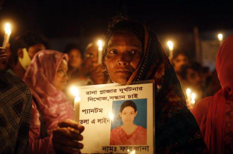 Uma mulher bengali segura o retrato de uma vítima.