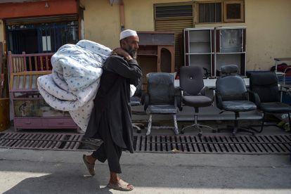 Um afegão vai ao mercado de segunda mão no bairro de Khari Khana, em Cabul, para vender um colchão e sua roupa de cama, no domingo.
