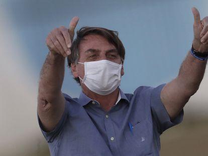 O presidente do Brasil, Jair Bolsonaro, de máscara e com os polegares erguidos, saúda o público em frente ao Palácio da Alvorada, sua residência oficial em Brasília, em 17 de julho, pouco depois de anunciar seu diagnóstico de covid-19.