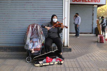 Mulher toca violino ao lado de seu bebê em uma rua de um setor comercial da capital.