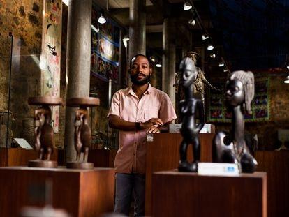 Igor Tiago, gestor cultura da Casa do Benin, no Pelourinho, em Salvador, posa em meio ao acervo do local.