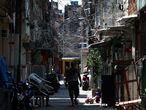 """ACOMPAÑA CRÓNICA: BRASIL CORONAVIRUS - AME1469. RIO DE JANEIRO (BRASIL), 15/10/2020.- Un hombre camina en la favela da Maré el 13 de octubre de 2020, en Rio de Janeiro (Brasil). Las calles volvieron a su dinámica en Maré. En medio de un comercio atiborrado y de la congestión del tráfico, este complejo de favelas en Río de Janeiro vive en plena pandemia una """"nueva normalidad"""". Pobreza y violencia permanecen, pero la solidaridad es ahora más visible. Pese al evidente abandono del Estado en una comunidad en la que impera la pobreza y donde la precariedad de servicios esenciales como la salud, el saneamiento básico y la seguridad son el pan de cada día, la gente del """"Complexo da Maré"""" no se rinde ante los retos que impone la covid-19. EFE/ Fabio Motta"""