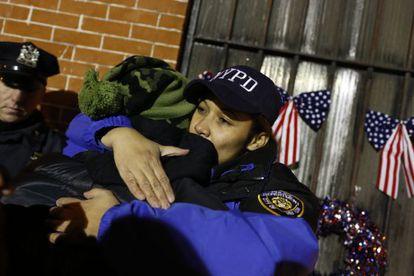 Uma policial abraça outra pessoa durante a vigília.