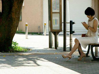Mulher aguarda em um ponto de ônibus.