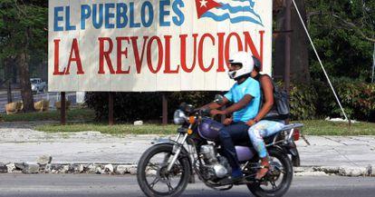 Motociclistas passam por cartaz alusivo à revolução cubana, em Havana.