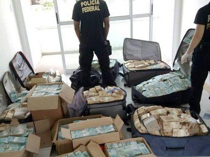 Policiais inspecionam montanhas de dinheiro achadas em Salvador.