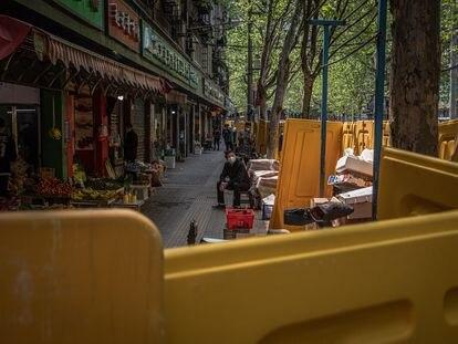 Um homem olha por trás das barreiras amarelas que ainda cercam muitas ruas da cidade.