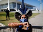 """TOPSHOT - A native of the Pataxo tribe with a painted arm that reads """"Bolsonaro resign"""" participates in a protest for the demarcation of land and against the government of the Brazilian President Jair Bolsonaro, in front of the Planalto Palace in Brasilia, on 17 June, 2021. (Photo by Sergio Lima / AFP)"""