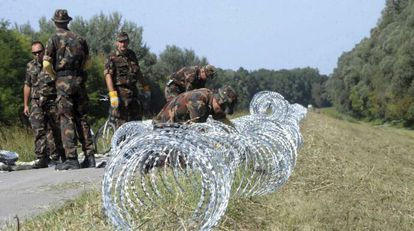 Soldados do Exército húngaro continuam construindo a cerca na fronteira com a Croácia, em 18 de setembro de 2015.