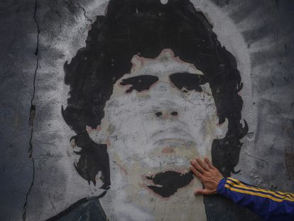 FILED - 25 November 2020, Argentina, Buenos Aires: A fan of the football club Boca Juniors puts his hand on a mural with the picture of the football star Diego Maradona on the day of his death. Argentina football great Diego Maradona has died at the age of 60, the Argentinian Football Association said on Wednesday. Photo: Fernando Gens/dpa