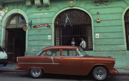 Um carro antigo estacionando em frente ao restaurante Casa Miglis.