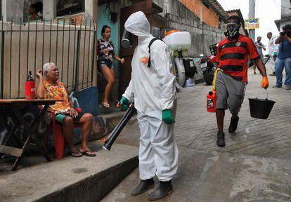Voluntário desinfeta uma área da favela da Babilônia, no Rio de Janeiro, no dia 18 de abril.