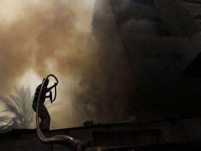 Um homem apaga as chamas de um incêndio provocado por um forte bombardeio em Gaza, em 30 de julho de 2014.
